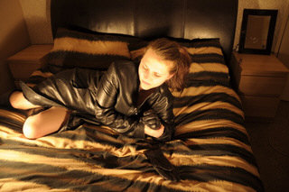 girl-in-leather-gloves-putting-on-leather-boots-in-leather-jacket-in-room